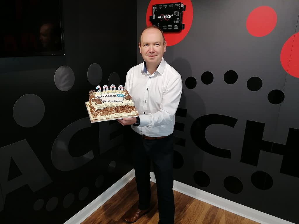 Eric Gallagher, ACETECH CEO, pictured holding a cake to celebrate LinkedIn milestone
